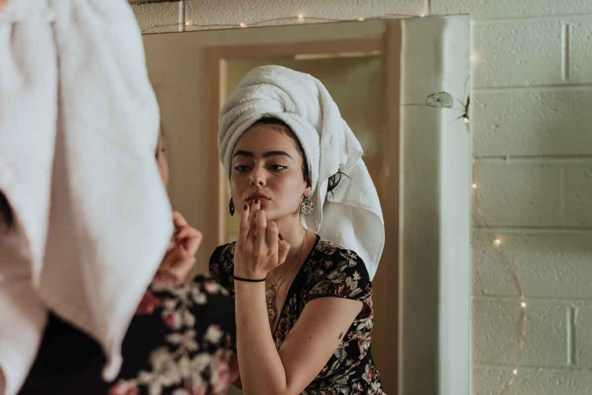 muger-maquillandose-en-espejo-de-aumento